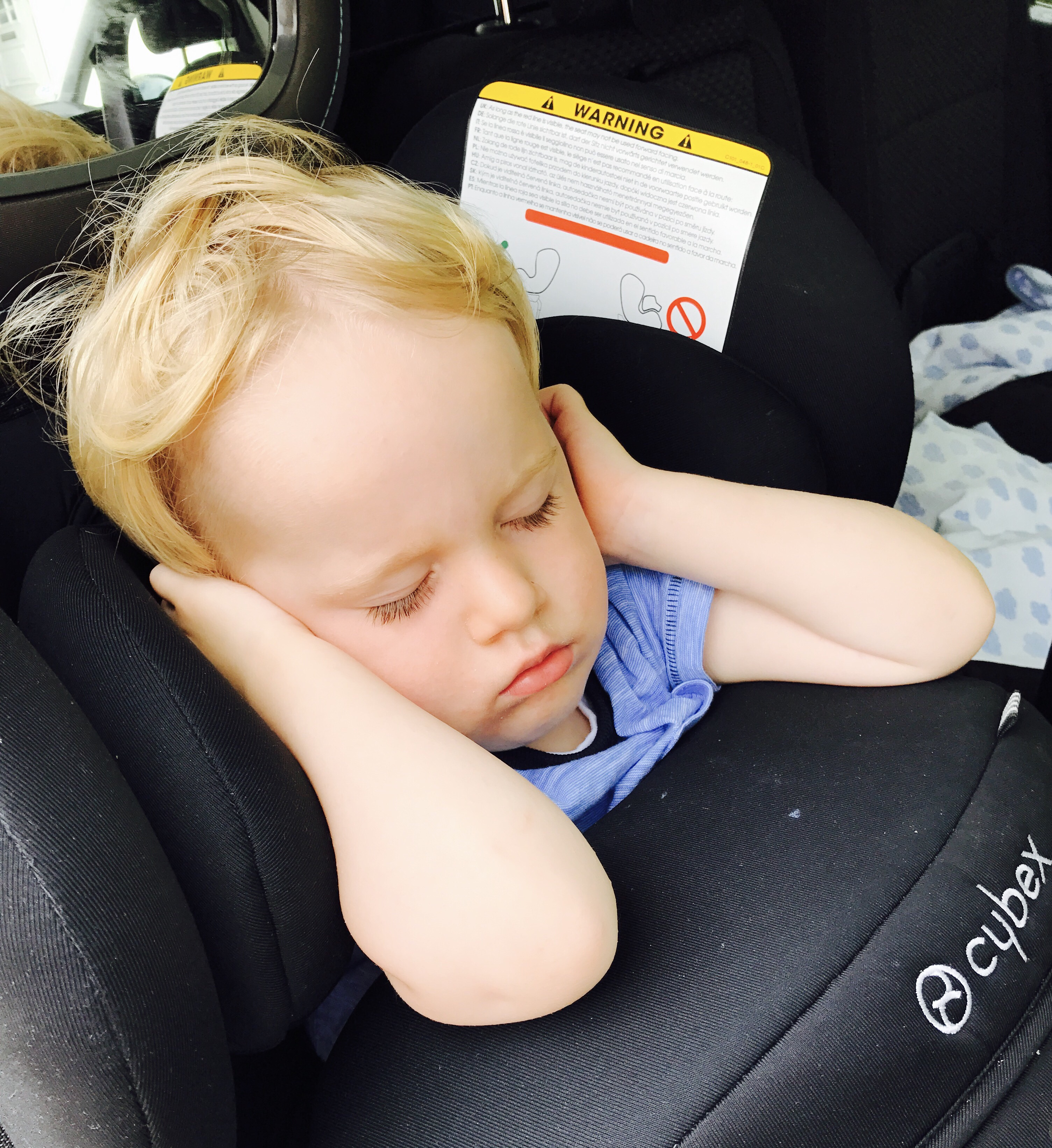 A toddler asleep in his car seat
