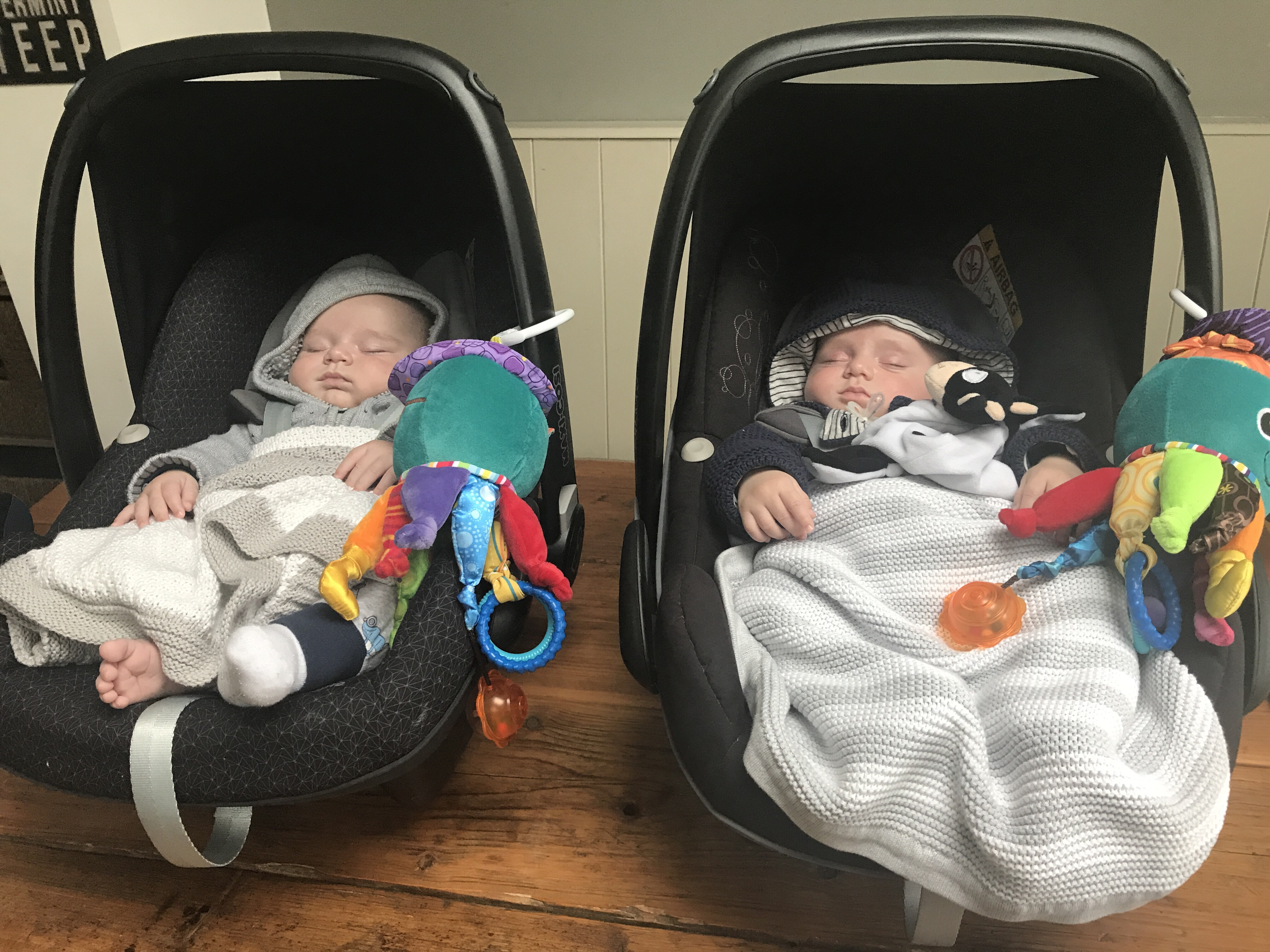 baby twins asleep in their car seats